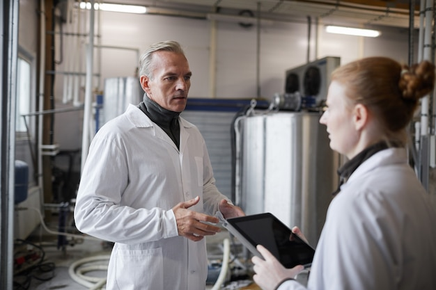 Waist up portrait of mature man instructing female worker while discussing work at food production factory, copy space
