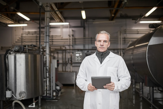 Waist up portrait of mature man wearing lab coat and looking at camera while working at food production, copy space
