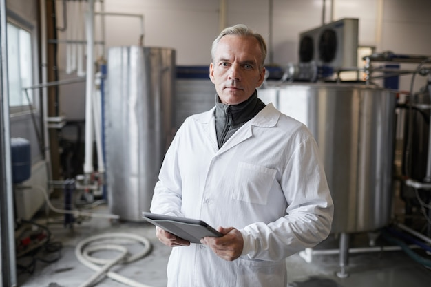 Waist up portrait of mature man wearing lab coat posing against machines while working at dairy factory, copy space