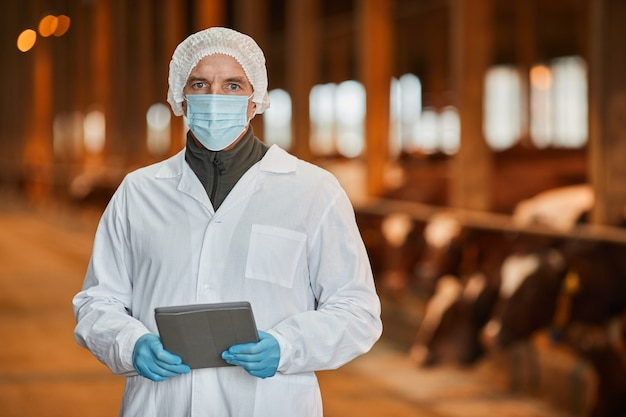 Waist up portrait of mature veterinarian wearing mask at farm and looking at camera while holding tablet