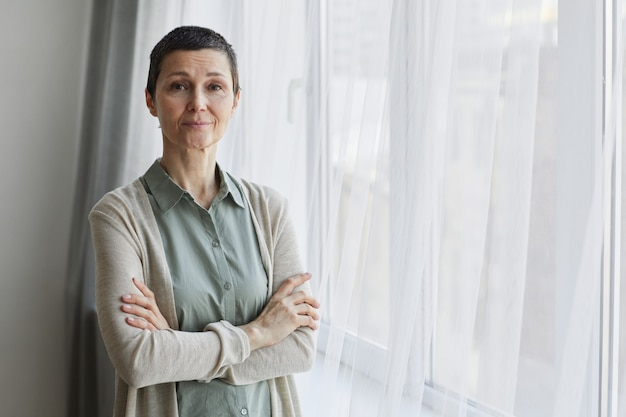 Waist up portrait of mature woman looking at camera while standing by window with arms crossed, copy space
