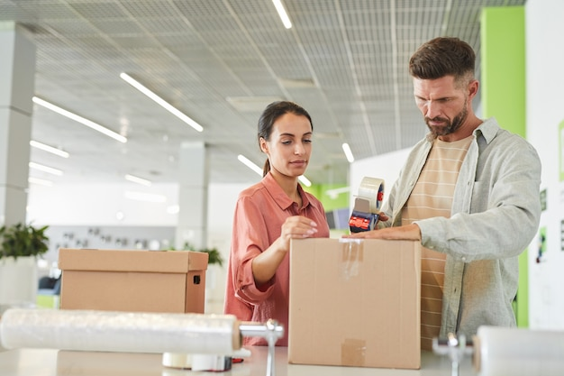 Waist up portrait of modern adult couple packing cardboard boxes with tape gun in storage facility or shipping service, copy space