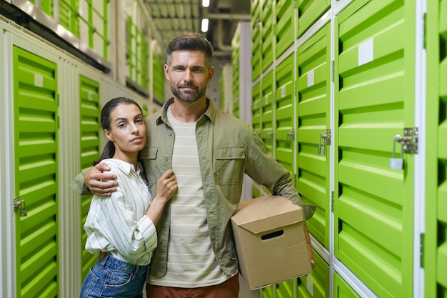 Waist up portrait of modern couple holding cardboard box standing in self storage facility and , copy space
