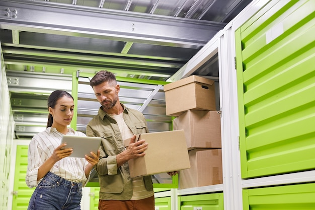 Waist up portrait of modern couple using digital tablet while loading boxes into self storage container, copy space