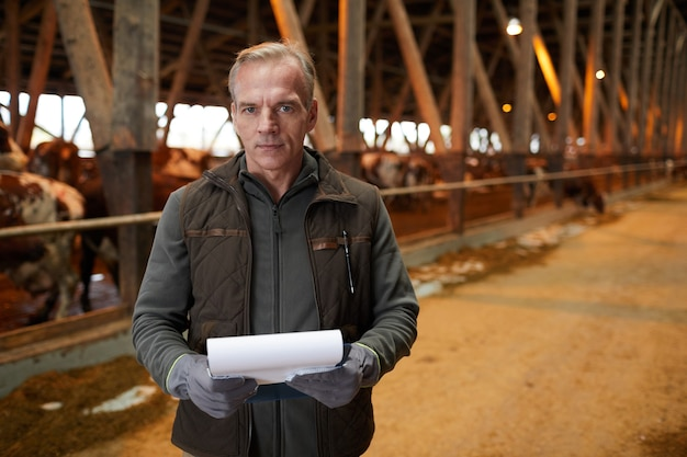 Waist up portrait of modern mature man holding clipboard and looking at camera while standing in livestock shed at family farm, copy space