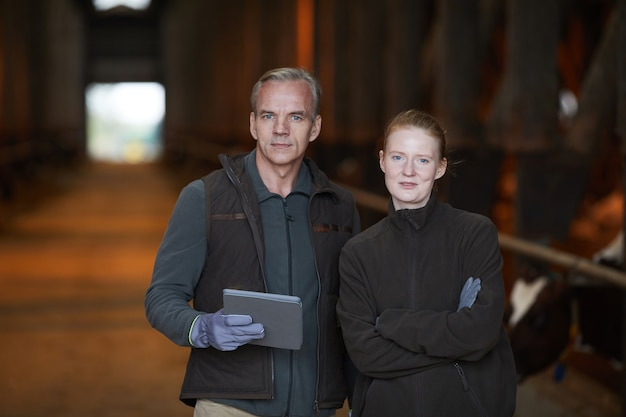 Waist up portrait of modern mature man posing with young daughter while working at family farm, copy space