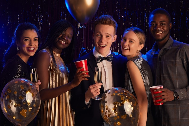 Waist up portrait of multi-ethnic group of friends smiling at camera happily while enjoying birthday party or prom night