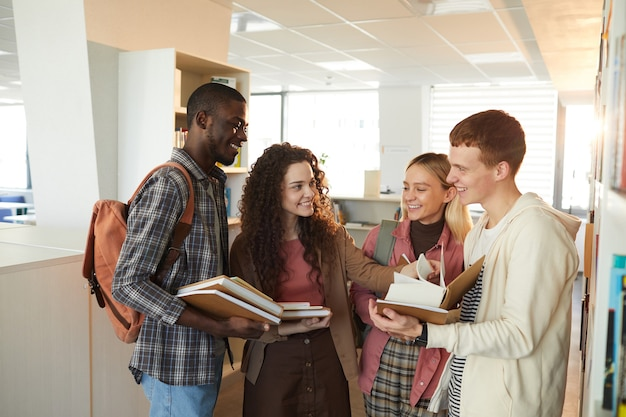Waist up portrait of multi-ethnic group of students chatting cheerfully while standing by shelves in school library lit by sunlight