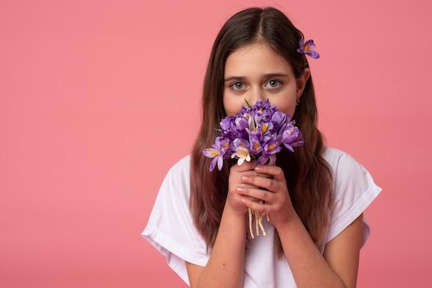 紫色の春の花で彼女の顔を隠す白いtシャツの美しいブルネットの少女の肖像画を腰に当てる