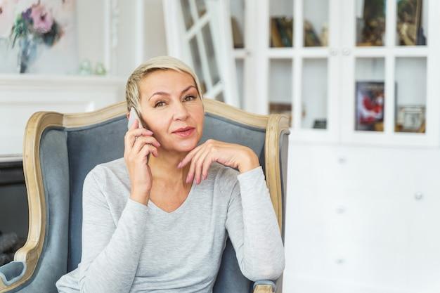 彼女の手であごを支えているリラックスした魅力的な年配の白人女性の腰の肖像画