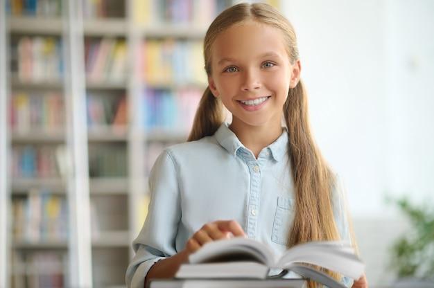 Портрет улыбающейся довольной красивой ученицы с хвостиками, позирующей перед камерой в публичной библиотеке