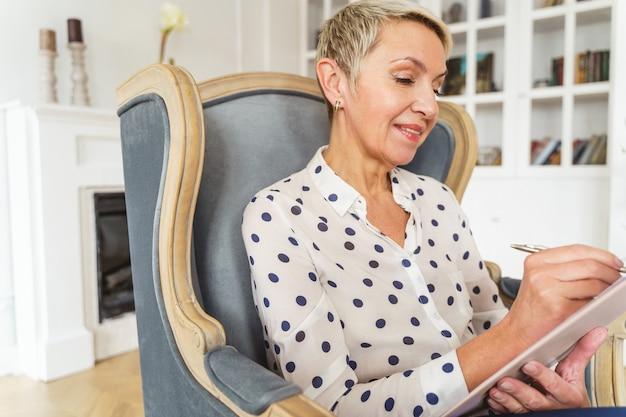 그녀의 사무실에서 환자와 함께 일하는 웃는 수석 여성 심리 치료사의 허리 위로 초상화