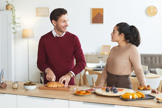 屋内でディナーパーティーのために料理をしながら楽しくおしゃべりする大人のカップルの肖像画を腰に当てて、