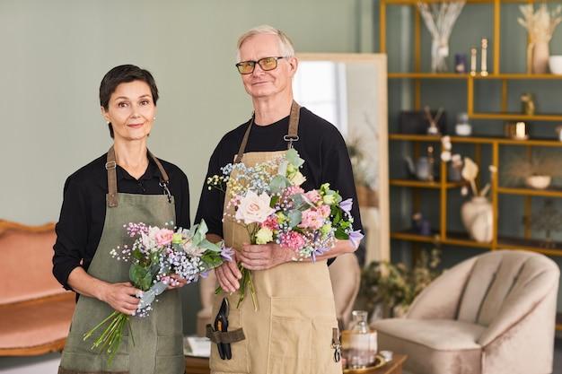 꽃집에 서서 꽃집을 바라보는 동안 꽃다발을 들고 있는 성인 꽃집 커플의 허리 위 초상화