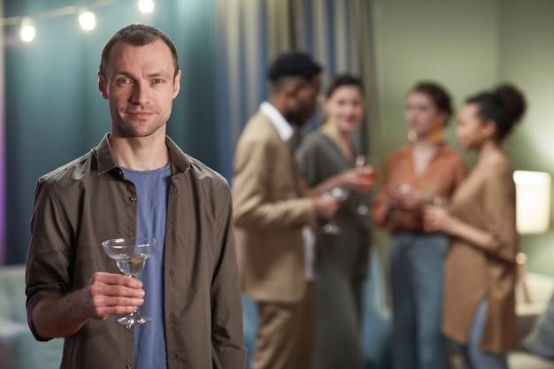 집에서 파티를 즐기는 동안 카메라를 보고 칵테일 잔을 들고 있는 성인 남성의 허리 초상화, 복사 공간