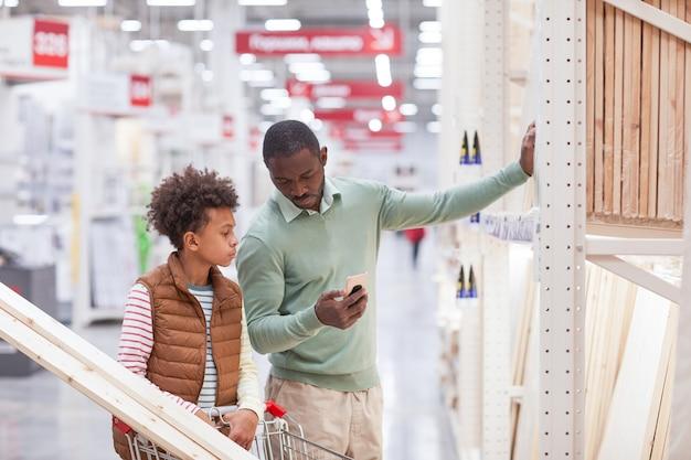 Портрет афро-американского отца и сына, поднимающегося вверх на талии, вместе делающих покупки в хозяйственном магазине и использующих смартфон, выбирая деревянные доски для улучшения дома