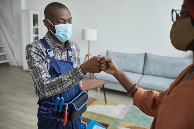 接触のない挨拶、コピースペースとしてクライアントと拳をぶつけるマスクを身に着けているアフリカ系アメリカ人の便利屋の肖像画を腰に当てる