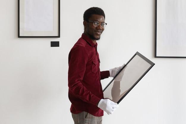 프레임을 잡고 아트 갤러리 또는 전시회를 계획하는 동안 아프리카 계 미국인 남자의 초상화를 허리 위로 올리십시오.