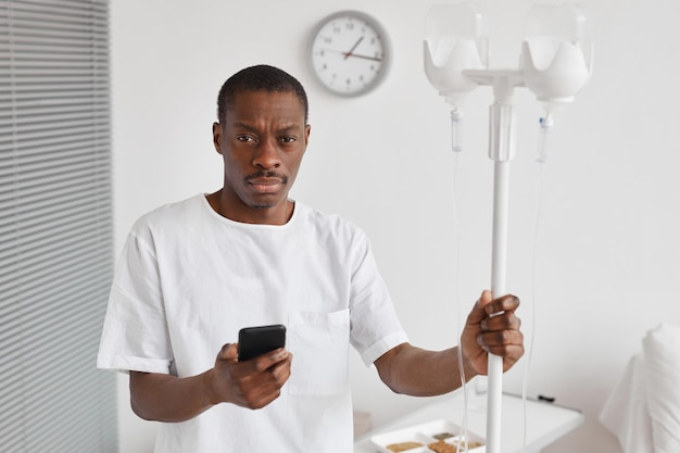 Портрет афро-американца, поднявшего талию, держится за подставку для капельницы во время лечения в больнице и смотрит в камеру, копировальное пространство