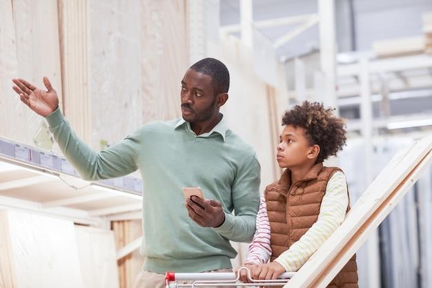 Талия вверх портрет афро-американского мужчины, указывающего на деревянные доски во время покупок с сыном в хозяйственном магазине, копия пространства