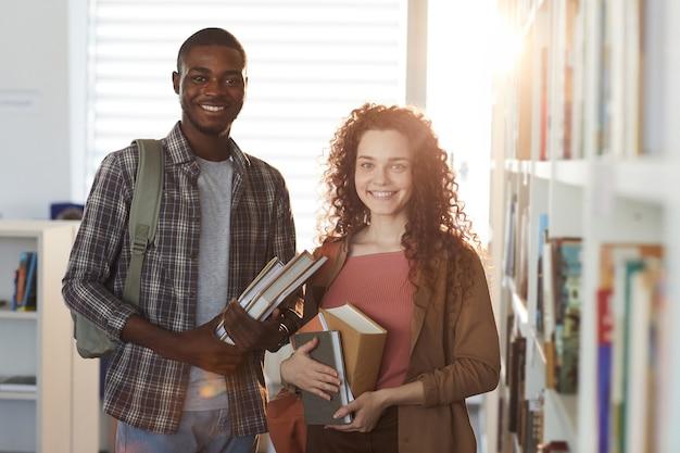 젊은 여자와 대학 도서관에 서있는 아프리카 계 미국인 남자의 초상화를 허리 위로, 책을 들고 카메라에 미소