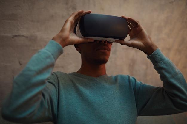 Портрет афроамериканца в костюме виртуальной реальности с приподнятым поясом, наслаждаясь иммерсивным опытом