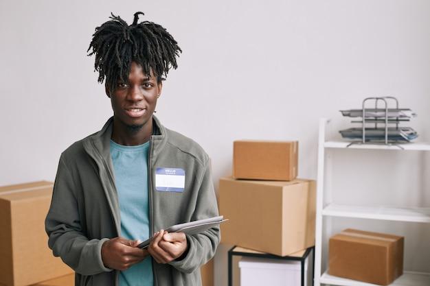 도움 및 기부 행사에서 상자를 정리하는 동안 태블릿을 들고 카메라를 바라보는 아프리카계 미국인 자원 봉사자의 허리 초상화