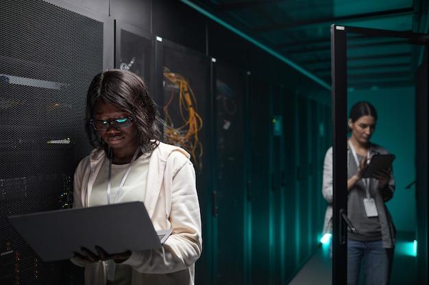 Подняв талию портрет афроамериканской женщины, использующей ноутбук в серверной комнате при настройке суперкомпьютерной сети, скопируйте пространство