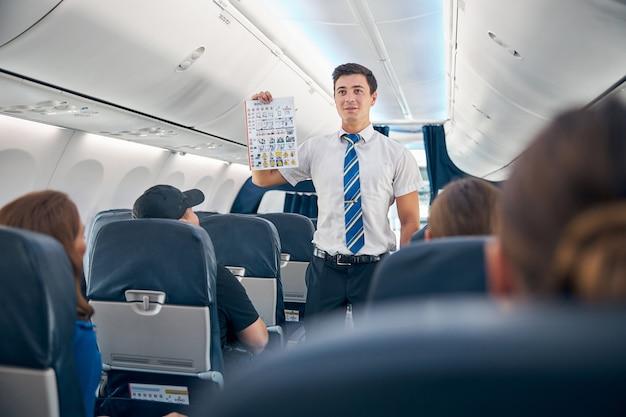 출발 전 상업용 여객기 승객에게 안전 절차를 설명하는 항공 승무원의 허리를 위로 올리십시오.