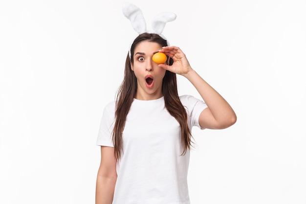 驚いたり驚いた若い女性のウエストアップの肖像画は、何か素晴らしいものを見て、目の上に色付きの卵を持って、ショックを受けたカメラを見つめ、あえぎ感動