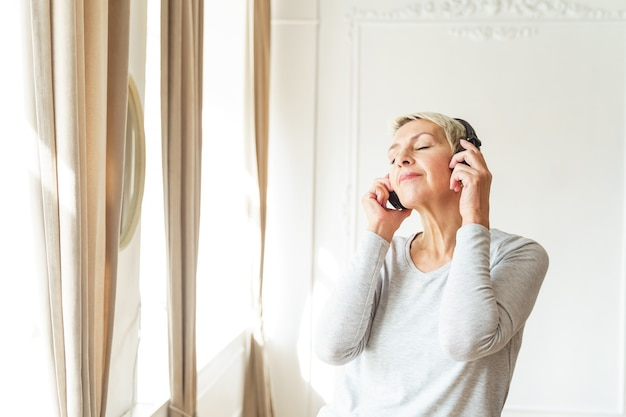 Портрет привлекательной пожилой женщины в наушниках, слушающей расслабляющую музыку