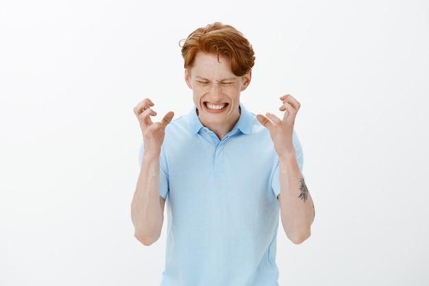 Поднятый вверх портрет раздраженного и рассерженного, разгневанного рыжего мужчины, сжимающего обеспокоенные пальцы