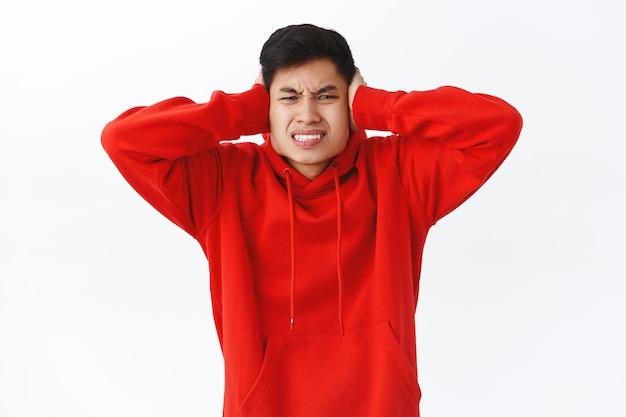 빨간 후드티를 입은 짜증나고 불쾌한 아시아 남성의 허리 위로 초상화는 이웃에게 볼륨을 낮추고, 귀를 닫고, 찡그린 얼굴을 하고, 짜증나는 시끄러운 소음을 듣고, 흰 벽에 서 있다고 말합니다.