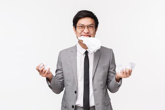 腹が立つ、腹を立てている怒っている若いアジア男性会社員、紙を食べる、顔をゆがめた積極的で苦しめられた、紙をリッピング、レポートを引き裂く、白い壁の上に立っての上半身の肖像