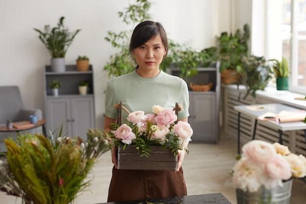 Талия вверх портрет азиатской молодой женщины, держащей цветы и смотрящей в камеру, позируя в мастерской флористов, копией пространства