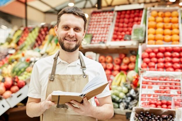 ファーマーズマーケットで果物や野菜のスタンドのそばに立っている間、エプロンを着て笑顔のひげを生やした男の肖像画を腰に当てる