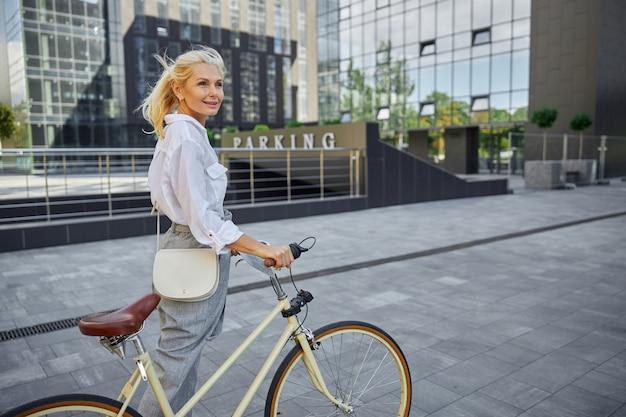 도시의 복고풍 자전거 핸들에 손을 잡고 있는 흰 블라우스를 입은 아름다운 금발 여성의 허리 위 초상화