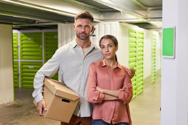 골판지 상자를 들고 셀프 스토리지 시설에서 아름다운 부부의 초상화를 허리 위로 복사 공간