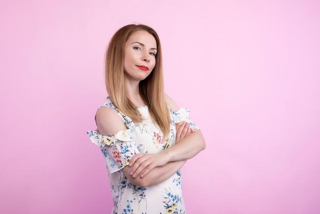 そばかすと髪の結び目がピンク色の壁に隔離され、テキスト用のコピースペースがあり、穏やかな表情でポーズをとっている美しいヨーロッパの20歳の女性の腰の肖像画。