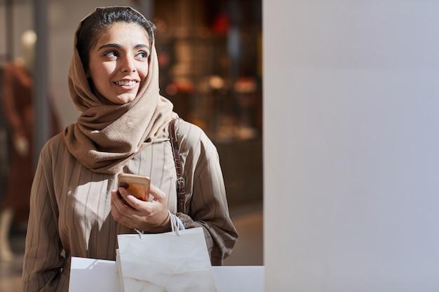 쇼핑몰에서 쇼핑을 즐기면서 멀리 햇빛에 의해 조명을 찾고 아름다운 중동 여자의 초상화를 허리, 복사 공간