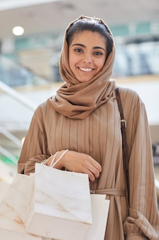 쇼핑몰에서 쇼핑을 즐기면서 아름다운 중동 여성의 초상화를 허리 위로