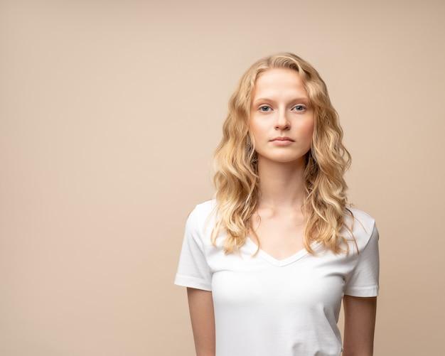 ベージュの壁に化粧なしで美しい若い深刻な賢いブロンドの女性の肖像画をウエストアップ