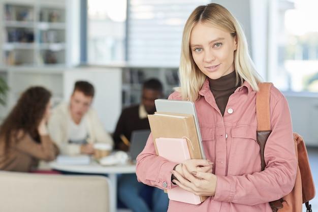 金髪の若い女性の肖像画を腰に上げ、バックグラウンドで働く人々と大学図書館に立っている間笑顔、、