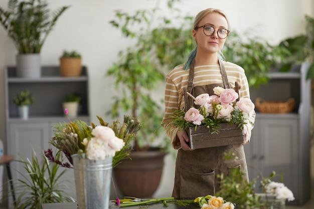花屋のワークショップでポーズをとっている間、花を持ってカメラを見ている金髪の若い女性の肖像画をウエストアップ、コピースペース