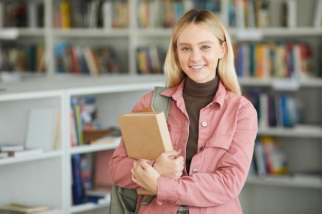 Талия вверх портрет молодой блондинки в школьной библиотеке, держащей книги и счастливо улыбаясь в камеру