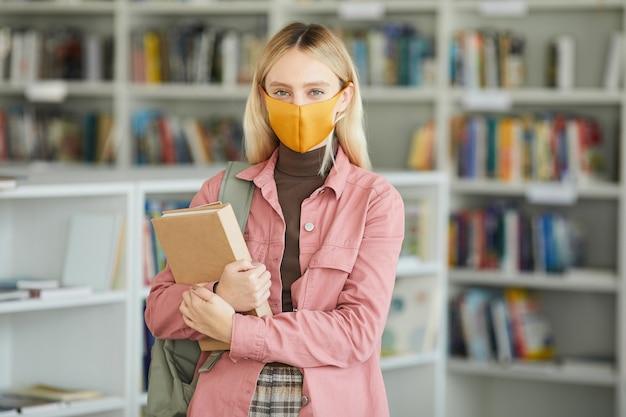 学校の図書館に立って本を持っている間、マスクを身に着けている金髪の若い女性の肖像画を腰に当て、