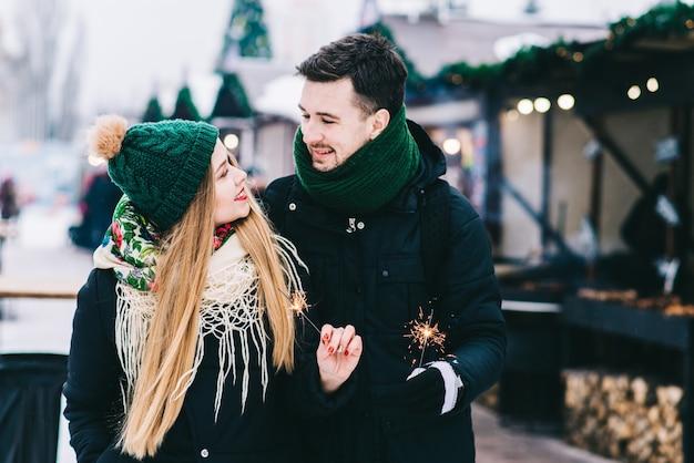 평온한 젊은 남자와 여자 껴안고 웃는 허리 위로 초상화. 그들은 겨울 거리에 서서 행복으로 서로를 바라보고 있다