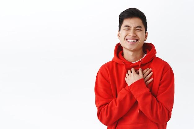 빨간 후드티를 입은 매력적인 아시아 남성의 허리 위 초상화, 감동과 감사, 웃고 웃고, 친구의 멋진 선물에 감사하고, 흰 벽에 서 있습니다.