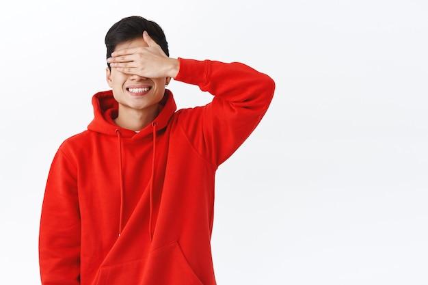 매력적인 젊은 아시아 남성의 허리 위로 초상화, 손바닥으로 눈을 감고 웃고, 깜짝 선물을 기다리고, 선물을 기대하고, 10을 세고, 숨바꼭질을 하고, 흰 벽에 서 있습니다.