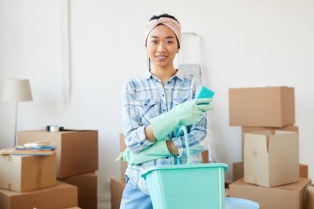 引っ越してきた後、新しい家やアパートを掃除しながら見ている陽気なアジアの女性の肖像画を腰に当てる